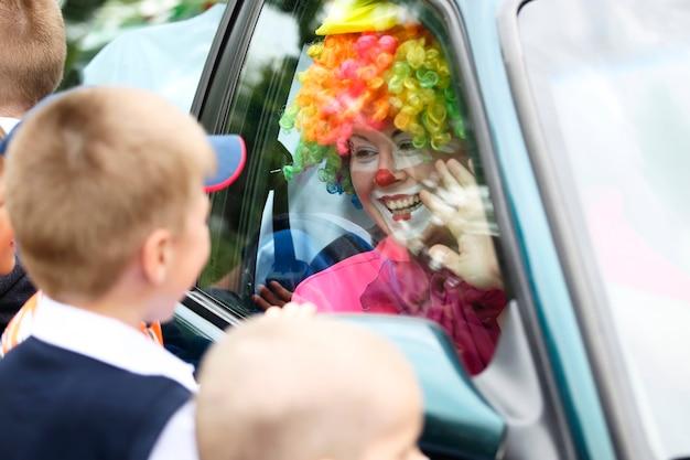 Der clown schaut durch das glas des autos nach fröhlichen kindern