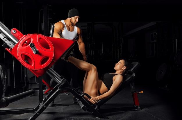 Der coach kontrolliert die ausführung der übung. vorbereitung eines athleten auf wettkämpfe.