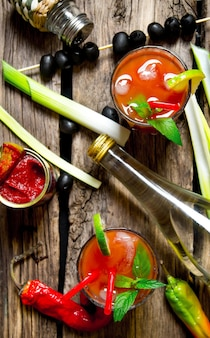 Der cocktail bloody mary. cocktail mit zutaten auf hölzernem hintergrund machen. draufsicht