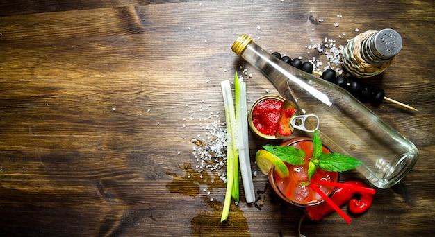 Der cocktail bloody mary. machen sie einen cocktail mit alkohol, tomatenmark und anderen zutaten auf holztisch. freier platz für text. draufsicht