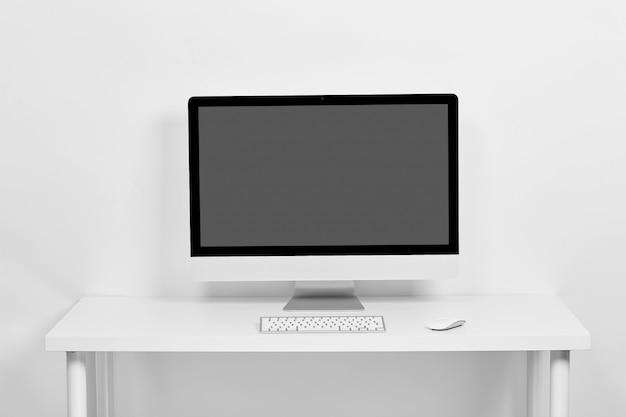 Der computer steht auf einem weißen tisch auf einem weißen, auf dem tisch stehen eine tastatur und eine computermaus