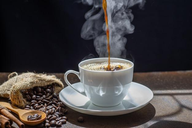 Der dampf vom eingießen des kaffees in die tasse, eine tasse frischen kaffees
