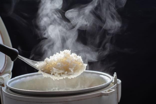 Der dampf vom mann, der geschmackvollen reis mit löffel vom kocher in der küche, jasminreis kocht im elektrischen reiskocher mit dampf nimmt. geringe tiefenschärfe,