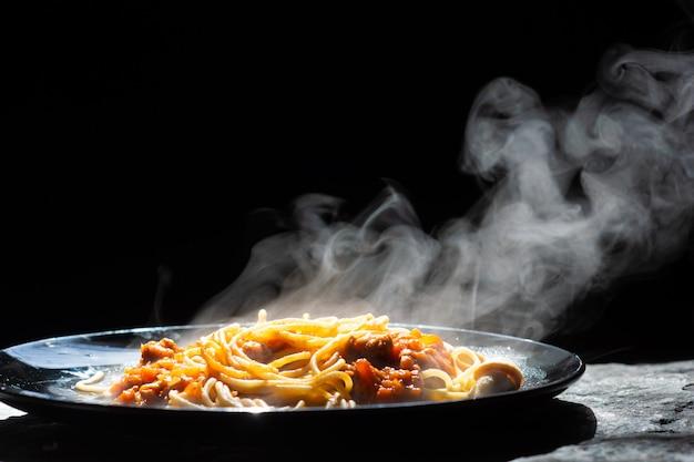 Der dampf von den spaghettis mit tomatensauce - selbst gemachte gesunde italienische teigwaren auf dunklem hintergrund