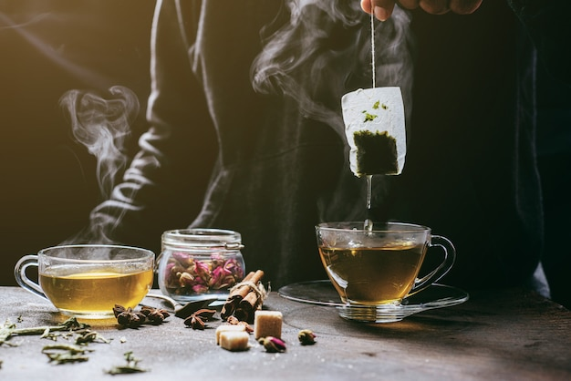 Der dampf von einem mann mit jeansjäckchen tränkt den teebeutel auf einer weißen vintage-tasse und bereitet heißen tee zu.