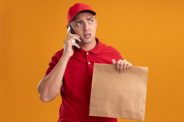 Der denkende blick auf den jungen lieferboten der seite, der uniform mit kappe hält, die papiernahrungsmittelpaket hält, spricht am telefon lokalisiert auf orange wand