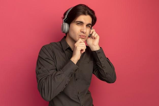 Der denkende junge, gutaussehende kerl, der ein schwarzes t-shirt mit kopfhörern trägt, packte das kinn isoliert an der rosa wand?