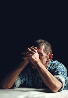 Der depressive ältere mann bedeckt sein gesicht mit den händen.