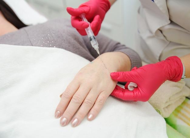 Der dermatologe der kosmetikerin führt eine sitzung zur mesotherapie oder biorevitalisierung und entfernung der pigmentierung an den händen alter frauen durch. einführung von hyaluronsäure unter die haut zur verjüngung.