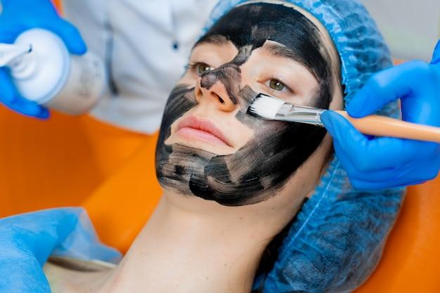 Der dermatologe schmiert eine schwarze maske auf das gesicht, um die laser zu verjüngen und das kohlenstoff-peeling durchzuführen. dermatologie und kosmetologie. mit einem chirurgischen laser.