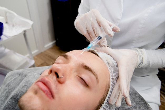 Der dermatologe spritzt dem menschen ins gesicht, um narben und falten zu entfernen und es glatt und jung zu machen.