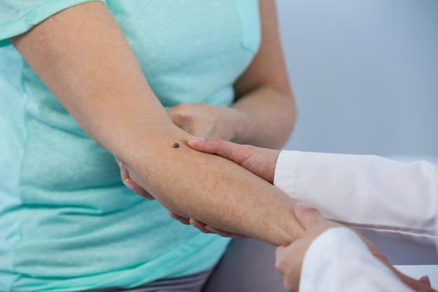 Der dermatologe untersucht einen maulwurf einer patientin