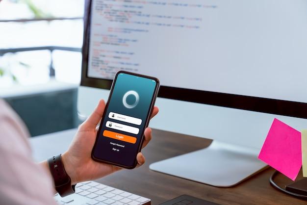 Der designer hält smartphone- und designanwendungen mit testleistung bereit, bevor er sie an kunden sendet. konzept des funktionierenden online-systems.