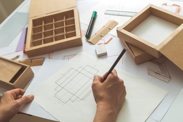 Der designer zeichnet skizzen für kartonverpackungen.