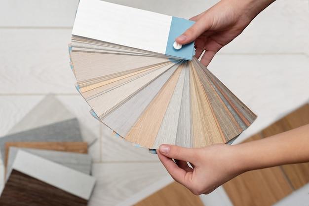 Der designerarchitekt hält eine palette von texturen und dekorationen für einen holzboden aus laminat und vinyl bereit. innenarchitektur. planung für reparaturen und hausbau.