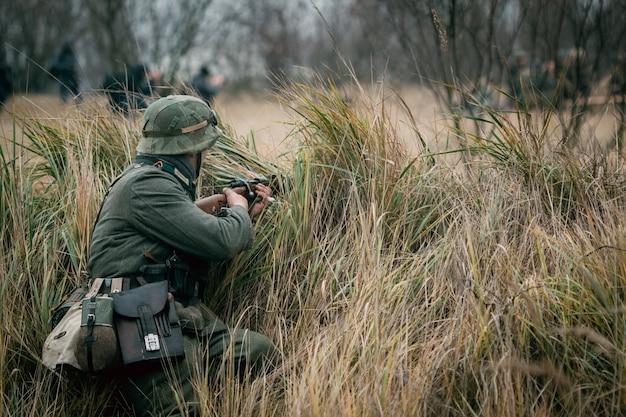 Der deutsche soldat wehrmacht sitzt mit einem gewehr im versteck