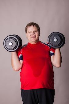 Der dicke mann macht sport. hantel und hantel heben