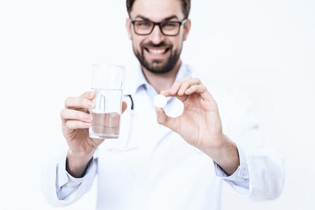 Der doktor im weißen kittel hält medizin.