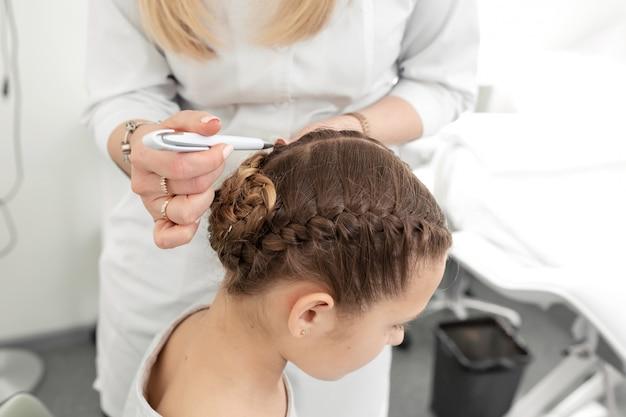 Der doktor-trichologe untersucht den zustand der haare eines teenagers