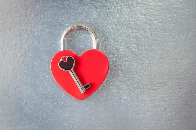 Der draufsichtschuß des roten herzvorhängeschlosses und -schlüssels auf silbernem hintergrund für valentinstag mit kopienraum. geschlossenes herzförmiges vorhängeschloss.