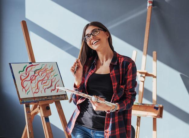 Der dunkelhaarige künstler hält einen pinsel in der hand und zeichnet ein bild auf leinwand.
