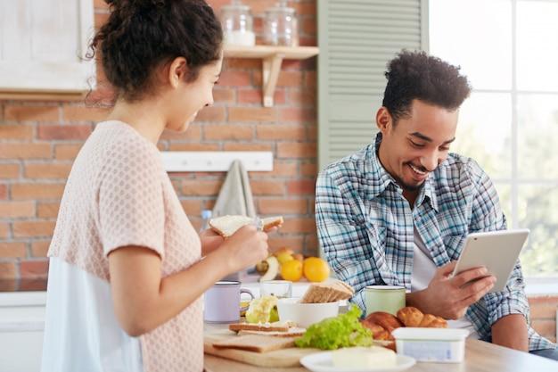 Der dunkelhäutige afroamerikaner sitzt lässig gekleidet in der küche mit tablet-computer und liest online nachrichten, wenn seine frau sandwiches macht.