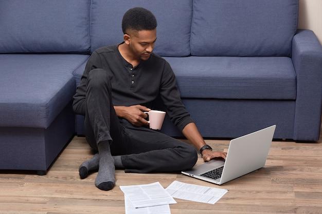 Der dunkelhäutige junge männliche erwachsene erledigt zu hause papierkram, studiert dokumente und hält einen becher mit heißem getränk