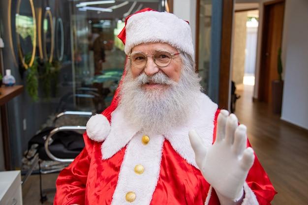 Der echte weihnachtsmann mit brille, handschuhen und hut, der direkt in die kamera schaut. nahaufnahme. der echte weihnachtsmann schaut in die kamera