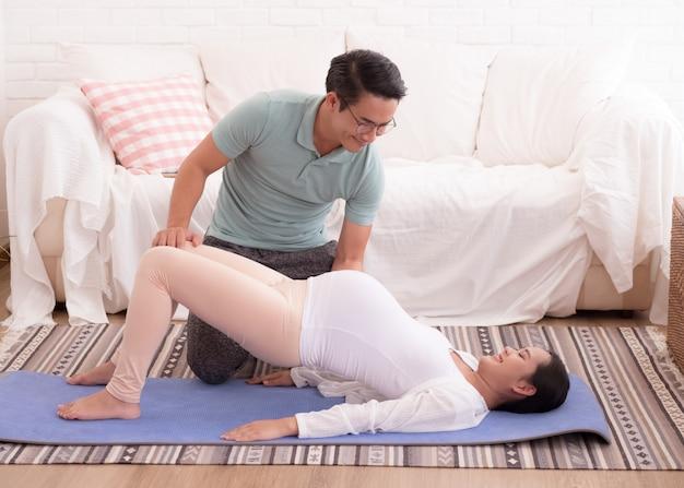 Der ehemann, der seiner schwangeren frau hilft, trainieren.