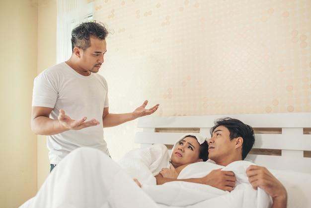Der ehemann fand mit seiner frau einen mann im schlafzimmer.