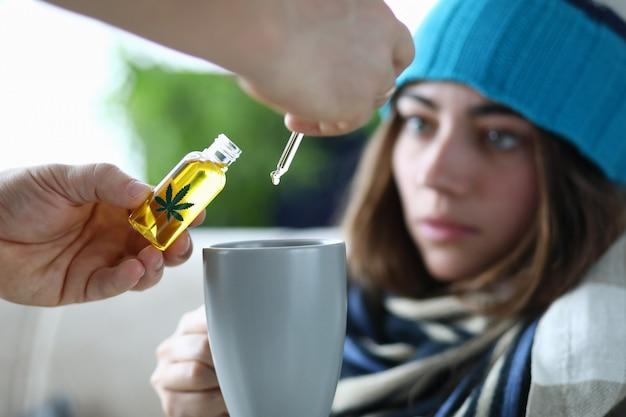 Der ehemann fügt der kranken frau im tee marihuanaöl-extrakt hinzu.