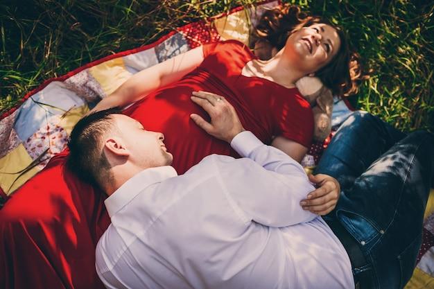 Der ehemann mit schwangeren frau liegt auf dem teppich
