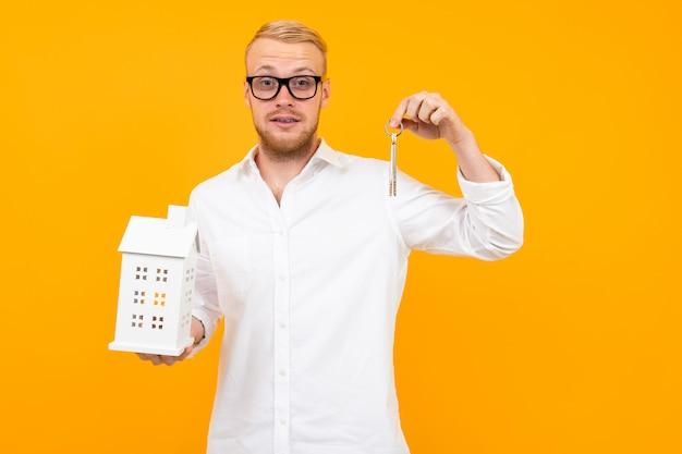 Der eigentümer der immobilie hält ein hausmodell und schlüssel in der hand auf einem gelb mit kopierraum