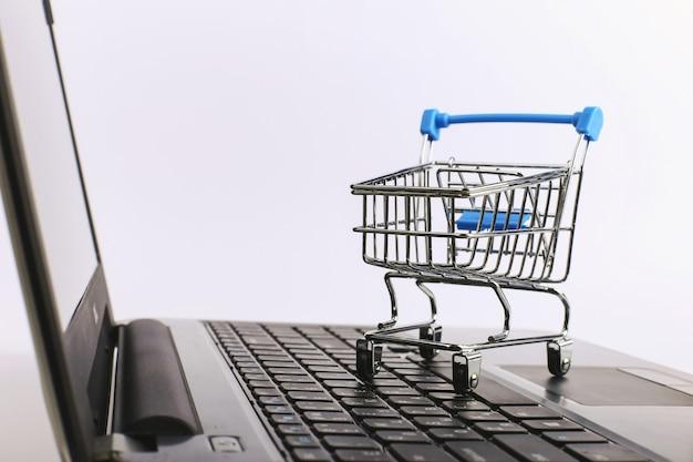 Der einkaufswagen befindet sich auf dem laptop. online-verkaufskonzept.