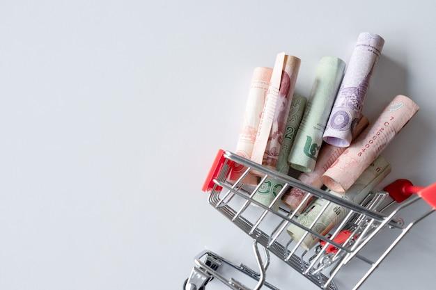 Der einkaufswagen mit dem geld (thailändisches geld) ist auf weiß verkehrt herum. draufsicht