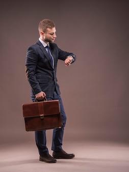Der elegante mann in einem anzug mit einer aktentasche, der auf seine uhr schaut