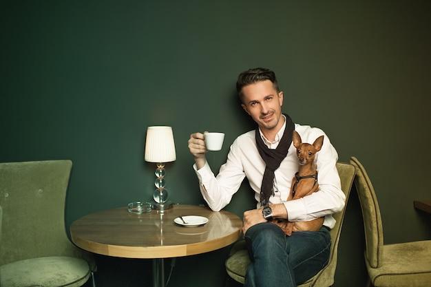 Der elegante mann mit einem kleinen hund an den händen, der im gemütlichen restaurant drinnen kaffee trinkt