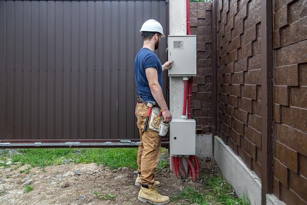 Der elektriker bei der arbeit untersucht die kabelverbindung in der elektrischen leitung im rumpf einer industriellen schalttafel. professionell in overalls mit einem elektrikerwerkzeug.
