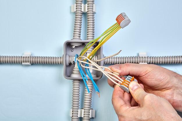 Der elektriker gruppiert die drähte mithilfe von federklemmen mit handhabungshebeln.