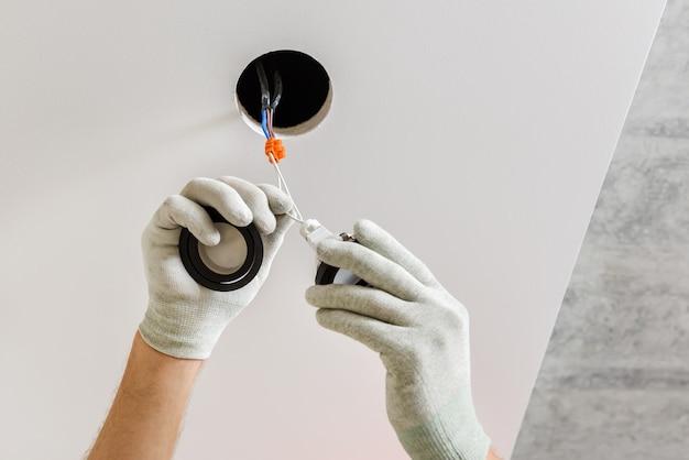 Der elektriker installiert led-strahler an der decke.