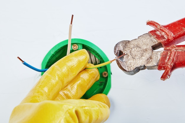 Der elektriker schneidet die enden der verkabelung des runden elektrokastens für den wandlichtschalter mit einem zangenwerkzeug ab.