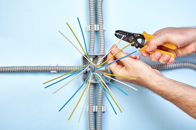 Der elektriker verwendet abisolierzangen, um die isolierung von der spitze jedes drahtes zu entfernen.
