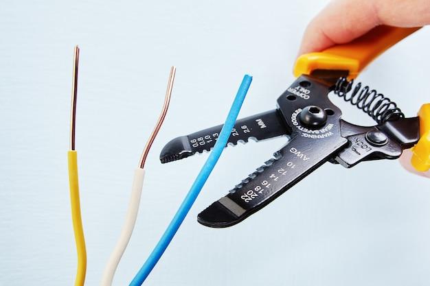 Der elektriker verwendet einen abisolierschneider, um die isolierung von der spitze jedes kabels während der elektrischen verkabelung zu entfernen.