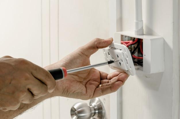 Der elektriker verwendet einen schraubenzieher, um das netzkabel an die steckdose anzuschließen.