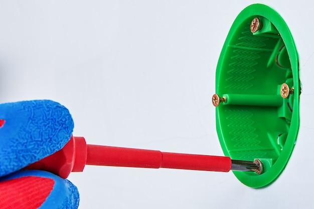 Der elektriker zieht die schraube im schaltkasten mit hilfe eines schraubendrehers fest.