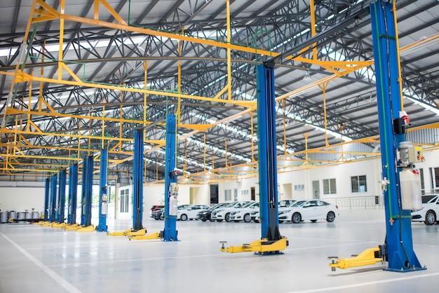 Der elektrische aufzug für autos im service wird im neuwagenfabrikservice auf den epoxidboden gelegt