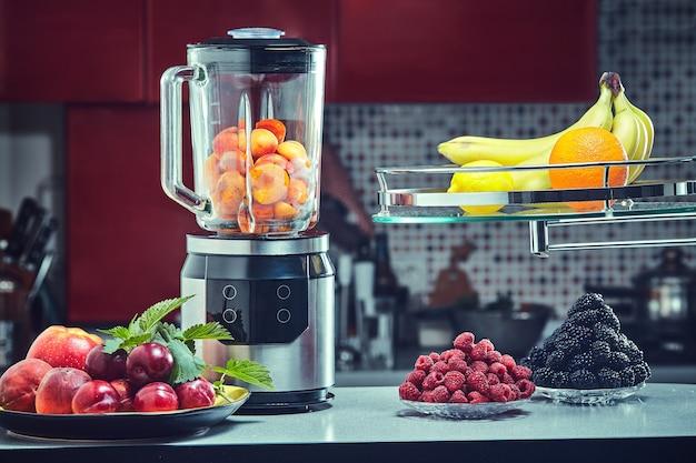Der elektrische mixer für fruchtsaft oder smoothie auf holzküchentisch.