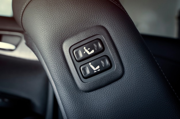Der elektrische sitzverstellknopf befindet sich an der seite des beifahrersledersitzes in einem luxusauto-autoteilekonzept.