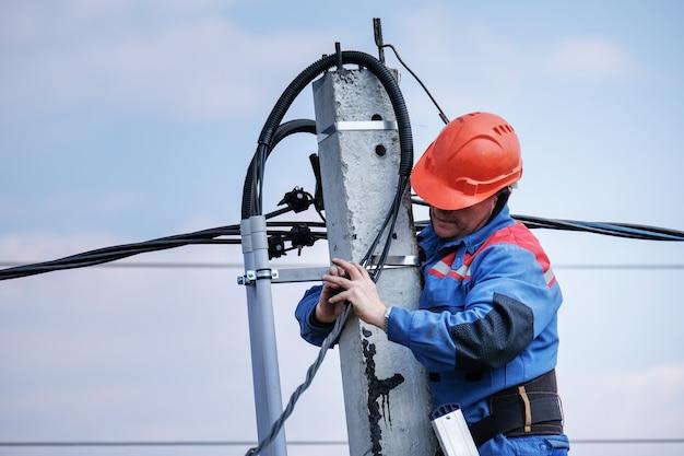 Der elektrotechniker führt die verkabelung an einem hohen mast durch, der auf der treppe steht. elektrische hochhausarbeiten. podkluchenie haus zu den stromleitungen