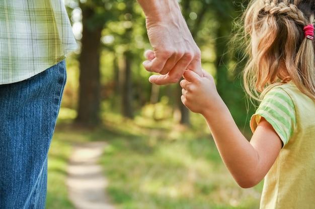 Der elternteil hält die hand des kindes mit einer glücklichen oberfläche